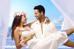 Dream wedding. Young men holding happy bride in arms after exotic wedding on tropical island Stock Photo