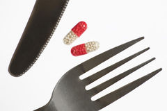 Dream about weight loss. Fork, knife and pill. White background Stock Photography