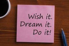 Dream it Wish it Do it written on note. Dream it, Wish it, Do it! written in note with pen and cup of coffee on wooden desk. Top view stock photos