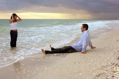 Dream woman coming out of ocean in front of man on. A young man is sitting on the beach at sunset as a sexy beautiful woman emerges from the water infront of him Royalty Free Stock Image