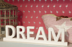 Dream wooden text over a shelf with pink background Stock Images