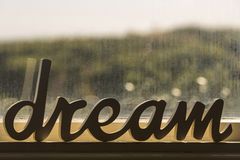 Dream Word. The word dream carved in wood, sitting on a beach house's window sill Stock Photography
