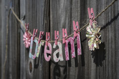 Dream. The word 'Dream' hanging on a string against a fence Royalty Free Stock Photos
