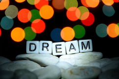 DREAM word. On top of rock formation with bokeh light background Stock Images