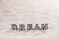 Dream word on white sand. Dream word silver and black on shiny white sand royalty free stock photos