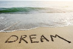 Dream word written on beach sand - positive thinking concept. Dream word written on the sand of the beach - positive thinking concept Royalty Free Stock Images