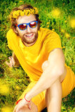 Dreamboat. Handsome young man sitting on a grass and smiles dreamily. Summer rest, vacation Royalty Free Stock Images