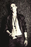 Dreamboat man. Fashion shot. Handsome sexual young man in leather jacket revealing his chest. Men`s beauty
