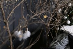 Dreamcatcher and branch trees against the background of a green fir-tree with white spheres and pieces of multi-colored pillows stock photos