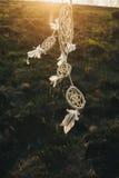 Dreamcatcher che pende da un albero in un campo al tramonto Immagine Stock