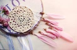 Dreamcatcher com penas e as rosas cor-de-rosa em um fundo de madeira Foto de Stock Royalty Free