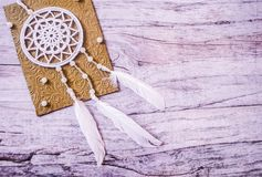 Dreamcatcher on embossed golden postcard worn wooden background stock image