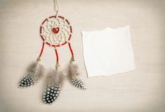 Dreamcatcher with feathers on a wooden background. Ethnic design, boho style, tribal symbol.Red heart as a symbol of Valentine`s. Dreamcatcher with feathers on a Royalty Free Stock Photo