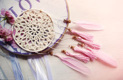 Dreamcatcher with pink feathers and roses on a wooden background. Ethnic design, boho style, tribal symbol Royalty Free Stock Photo