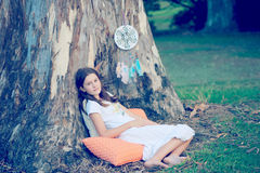 Dreamcatcher. Pretty girl comfortably sitting under a large tree where hangs a pretty dream catcher made of old vintage crochet doily, beads and feathers Royalty Free Stock Image