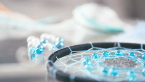 `Dreamcatcher` - a product of the thread, decor element. Close-up of Dreamcatcher black thread and turquoise beads lies on a glass background, turquoise beads stock footage