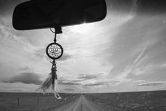 Dreamcatcher on a Rearview. A dreamcatcher hung on a car rearview mirror Stock Image