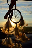 Dreamcatcher. A dreamcatcher on window with sunset on the bachground Stock Image
