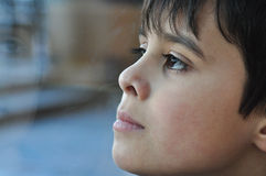 Dreamer. Thoughtful little boy looking out the window. Perfect for text insertion. Reflection of right side of face in glass Royalty Free Stock Photos