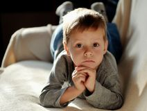 Dreamer. On the sofa lay a little boy in the sun than the upset Royalty Free Stock Image