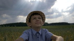 Dreamer boy in the hat looks at the beautiful sky in the field. Have fun stock photography