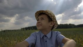 Dreamer boy in the hat looks at the beautiful sky in the field. Have fun royalty free stock photo