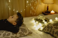 Dreamer boy lying in bed evening in dark against the background. Of lanterns Royalty Free Stock Photos