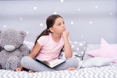 Dreamer concept. Cute little dreamer. Dreamer girl dream in bed. Child dreamer with book and teddy bear. Childhood dream royalty free stock photos