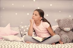 Dreamer concept. Cute little dreamer. Dreamer girl dream in bed. Child dreamer with book and teddy bear. Childhood dream.  royalty free stock images
