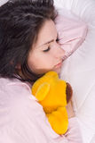 Dreamer. Girl sleeping with teddy bear in bed stock photo