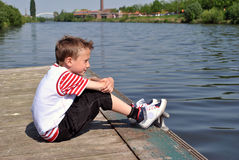 Dreamer kid. Kid dreaming with next to the river Royalty Free Stock Photo