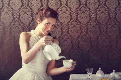 Dreamer woman drinking tea at tea time. In dining room Stock Image