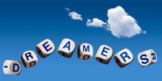 Dreamers concept using spelling letters on blue sky. Dreamers children spelling letters on blue sky to illustrate dreaming of the future Royalty Free Stock Photo