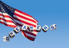 Dreamers concept using spelling letters against blue sky and flag. Dreamers children spelling letters on blue sky and USA flag to illustrate dreaming of the Royalty Free Stock Photos