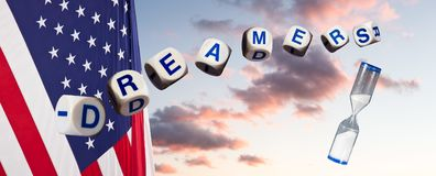 Dreamers in spelling letters against sunset sky and flag and hourglass royalty free stock photos