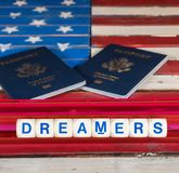Dreamers concept using spelling letters on US flag. Dreamers children spelling letters on wooden USA flag with passports for citizenship Royalty Free Stock Photos