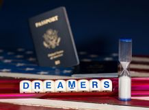 Dreamers concept using spelling letters on and hourglass. Dreamers children spelling letters on wooden USA flag with passports for citizenship and hourglass Royalty Free Stock Images