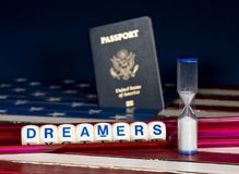 Dreamers concept using spelling letters and hourglass. Dreamers children spelling letters on wooden USA flag with passports for citizenship and hourglass Stock Images