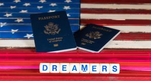 Dreamers concept using spelling letters on US flag. Dreamers children spelling letters on wooden USA flag with passports for citizenship Royalty Free Stock Image