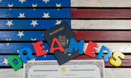 Dreamers concept using spelling letters on US flag. Dreamers concept on wooden USA flag with passport and naturalization certificate Stock Images