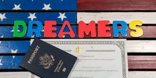 Dreamers concept using spelling letters on US flag. Dreamers concept on wooden USA flag with passport and naturalization certificate Royalty Free Stock Photography