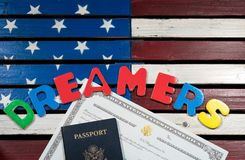 Dreamers concept using spelling letters on US flag. Dreamers concept on wooden USA flag with passport and naturalization certificate Stock Photo