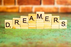 Dreamers immigration concept spelled out in block letters. Dreamers immigration concept spelled out in stacked block letters with brick wall in background Royalty Free Stock Images
