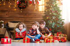 Dreamers. Kids with Christmas gift. Background Christmas tree Stock Photography