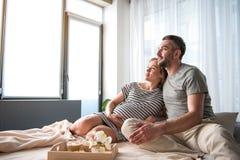 Dreamful gravid kvinna som kopplar av på sängkläder med hennes make royaltyfria foton
