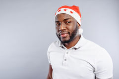 Dreamful guy standing in Santa Claus hat Stock Images