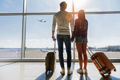 Dreamful loving couple looking at flying plane. We are ready for new future. Young men and women are watching flight at airport. They are standing and carrying Royalty Free Stock Photos