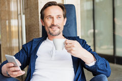 Dreamful man enjoying hot beverage in cafeteria. Portrait of relaxed businessman drinking coffee with pleasure while sitting on comfortable armchair. He is Stock Image