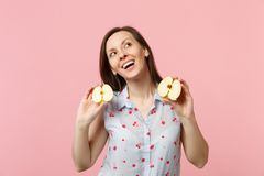 Dreamful pretty young woman in summer clothes looking up holding halfs of fresh ripe apple fruit isolated on pink pastel