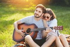 Dreamful romantic couple sit on green grass, enjoy togetherness. Handsome bearded man plays guitar and her girlfriend leans at his. Dreamful romantic couple sit stock photo